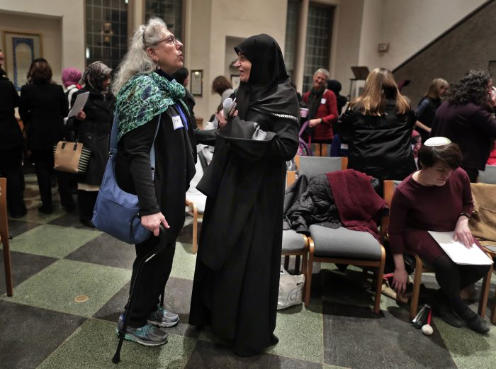 In this Thursday, Feb. 16, 2017 photo, members of the Sisterhood Salaam Shalom talk after a unity vigil held at the Jewish Theological Seminary in New York. The Sisterhood of Salaam Shalom, a national organization that brings together Muslim and Jewish women, organized the gathering as part of the organization's response to President Donald Trump's travel ban. (AP Photo/Julie Jacobson)