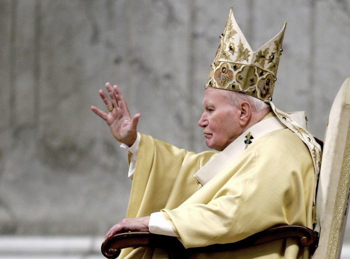 """FILE- In this Saturday, Jan. 1, 2005 file photo, Pope John Paul II delivers his blessing as he enters St. Peter's Basilica at the Vatican to preside a New Year's Day mass. A book of interviews with the Polish Rev. Mieczyslaw Mokrzycki, """"Secretary of Two Popes,"""" released May 2017, has offered some insight into the daily life at the Vatican with John Paul and his German-born successor, Benedict XVI.  (AP Photo/Andrew Medichini, File)"""