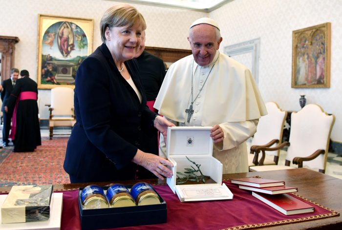 Pope Francis and German Chancellor Angela Merkel exchange gifts on the occasion of their private audience, at the Vatican, Saturday, June 17, 2017. (Ettore Ferrari/Pool Photo via AP)