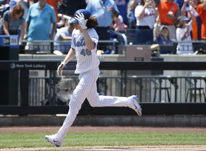 New York Mets starting pitcher Jacob deGrom holds his batting helmet as he rounds the bases after hitting a solo home run during the third inning of a baseball game against the New York Mets, Sunday, June 18, 2017, in New York. (AP Photo/Kathy Willens)