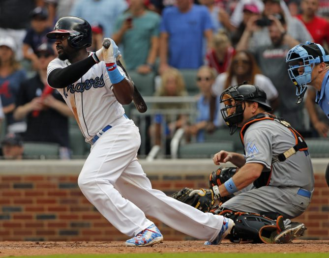 Atlanta Braves' Brandon Phillips drives in the game-winning run with a base hit as Miami Marlins catcher A.J. Ellis (17) looks on in the ninth inning of a baseball game Sunday, June 18, 2017, in Atlanta. Atlanta won 5-4. (AP Photo/John Bazemore)