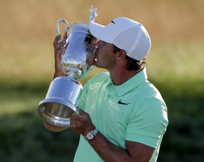 Brooks Koepka kisses the winning trophy after the U.S. Open golf tournament Sunday, June 18, 2017, at Erin Hills in Erin, Wis. (AP Photo/Chris Carlson)