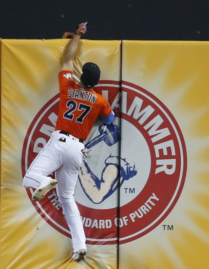 Miami Marlins right fielder Giancarlo Stanton loses his glove over the wall as he attempted to catch a triple hit by Los Angeles Dodgers' Chris Taylor during the fourth inning of a baseball game, Sunday, July 16, 2017, in Miami. The Dodgers defeated the Marlins 3-2. When Stanton made a running leap and stretched his left arm above the wall, his glove came off and fell to the other side. (AP Photo/Wilfredo Lee)