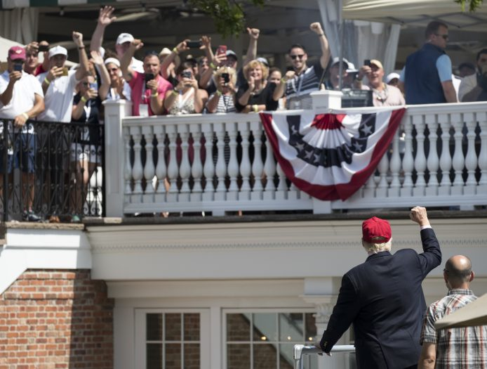 President Donald Trump turns to the clubhouse crowd as he arrives to enter his presidential viewing stand, Sunday, July 16, 2017, during the U.S. Women's Open Golf tournament at Trump National Golf Club in Bedminster, N.J. (AP Photo/Carolyn Kaster)