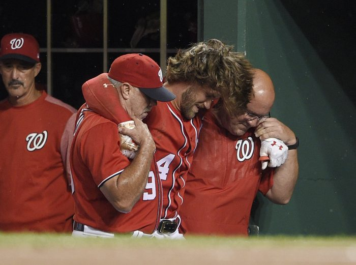 Washington Nationals' Bryce Harper, center, is helped in the dugout after he was injured during the first inning of the team's baseball game against the San Francisco Giants, Saturday, Aug. 12, 2017, in Washington. (AP Photo/Nick Wass)
