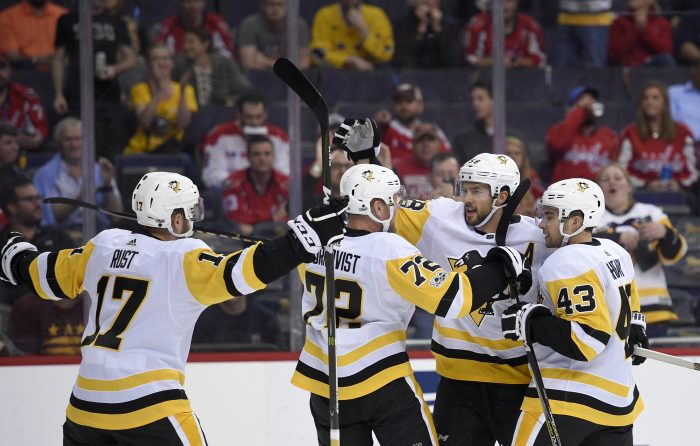 Pittsburgh Penguins defenseman Kris Letang (58) celebrates his goal with Conor Sheary (43), Patric Hornqvist (72) and Bryan Rust (17) during the first period of an NHL hockey game against the Washington Capitals, Wednesday, Oct. 11, 2017, in Washington. (AP Photo/Nick Wass)