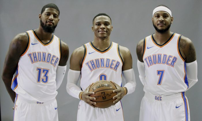 FILE - In this Sept. 25, 2017, file photo, Oklahoma City Thunder's Paul George (13), Russell Westbrook, center, and Carmelo Anthony (7) pose for a photo during an NBA basketball media day in Oklahoma City. Westbrook is a two-time scoring champion, two-time All-Star MVP and the reigning league MVP. Anthony is a 10-time All-Star and three-time Olympic gold medalist. George is a four-time All-Star, former Most Improved Player and an Olympic gold medalist. None of the new Oklahoma City Thunder teammates have an NBA title. (AP Photo/Sue Ogrocki, File)