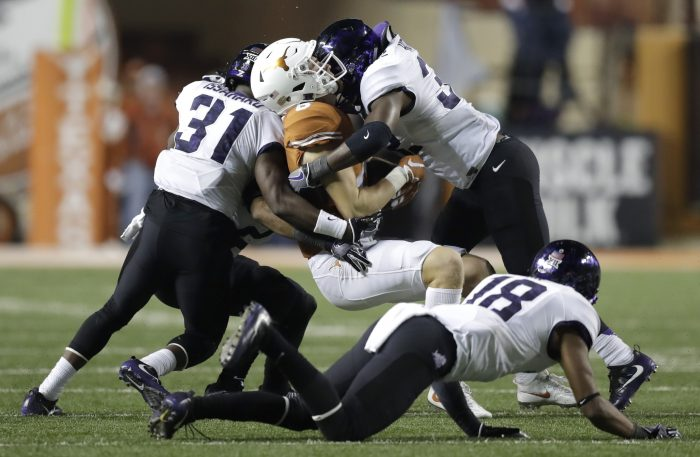 FILE - In this Nov. 25, 2016, file photo, Texas wide receiver Jake Oliver, center, is hit by TCU defenders Ridwan Issahaku (31) and Travin Howard (32) after making a catch during the second half of an NCAA college football game, in Austin, Texas. Patterson's defense is a formula that opposing coaches in the Big 12, and all those big-play and fast-paced offenses, have been trying to figure out since the Horned Frogs moved into the league in 2012. (AP Photo/Eric Gay, File)
