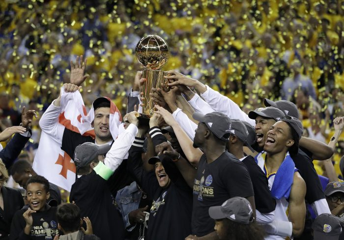 FILE - In this June 12, 2017, file photo, Golden State Warriors players, coaches and owners hold up the Larry O'Brien NBA Championship Trophy after Game 5 of basketball's NBA Finals between the Warriors and the Cleveland Cavaliers in Oakland, Calif. Winners of the NBA title in two of the last three seasons, Golden State made it look easy at times a year ago and prevailed in 31 of their final 33 games.  (AP Photo/Marcio Jose Sanchez, File)