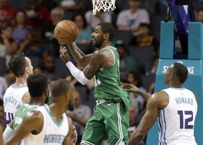Boston Celtics' Kyrie Irving (11) drives between Charlotte Hornets' Dwight Howard (12) and Frank Kaminsky (44) in the second half of a preseason NBA basketball game in Charlotte, N.C., Wednesday, Oct. 11, 2017. (AP Photo/Chuck Burton)