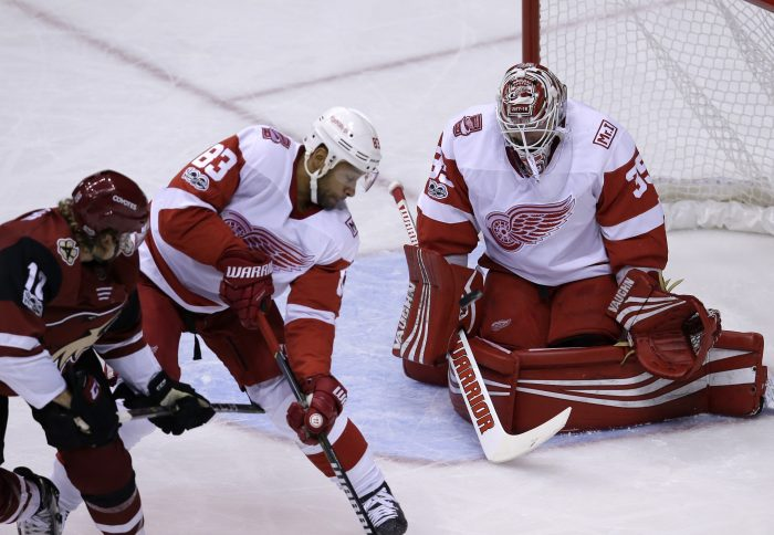 Detroit Red Wings right wing Anthony Mantha (39) makes a save against Arizona Coyotes center Christian Dvorak (18) as Trevor Daley (83) defends in the first period during an NHL hockey game, Thursday, Oct. 12, 2017, in Glendale, Ariz. (AP Photo/Rick Scuteri)