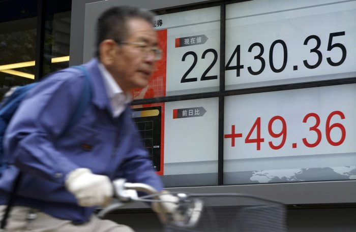 A man rides a bicycle past an electronic stock board showing Japan's Nikkei 225 index at a securities firm in Tokyo Tuesday, Nov. 14, 2017. Asian shares were mostly lower Tuesday as markets watched for tax reform developments in the U.S. and digested economic data from China. (AP Photo/Eugene Hoshiko)
