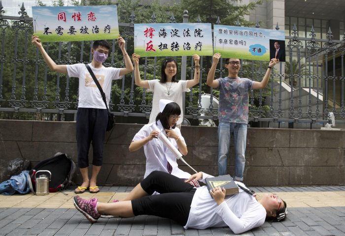 """FILE - In this July 31, 2014, file photo, gay rights campaigners act out electric shock treatment to protest outside a court where the first court case in China involving so-called conversion therapy is held in Beijing, China. Human Rights Watch says Wednesday, Nov. 15, 2017, in a new report that the Chinese government should stop hospitals and other medical facilities from subjecting LGBT people in China to conversion therapy that in some cases has involved electroshocks, involuntary confinement and forced medication. The banners from left read """"Gays, no need to be treated,"""" """"Support Haidian Court, Against twisted treatment,"""" and """"Ms. Baidu promotes gay treatment by Li Yanhong (Chairman of Baidu)."""" (AP Photo/Ng Han Guan, File)"""
