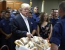 President Donald Trump prepares to hand out sandwiches to members of the U.S. Coast Guard at the Lake Worth Inlet Station, on Thanksgiving, Thursday, Nov. 23, 2017, in Riviera Beach, Fla. (AP Photo/Alex Brandon)