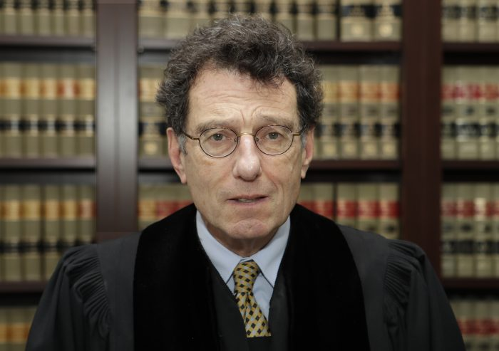 Judge Dan Polster poses in his office, Thursday, Jan. 11, 2018, in Cleveland. Polster has invited Ohio's attorney general Mike DeWine to brief him on the impact of the opioid epidemic. Polster is overseeing a consolidated case involving dozens of lawsuits filed by communities around the country against drugmakers and drug distributors. (AP Photo/Tony Dejak)