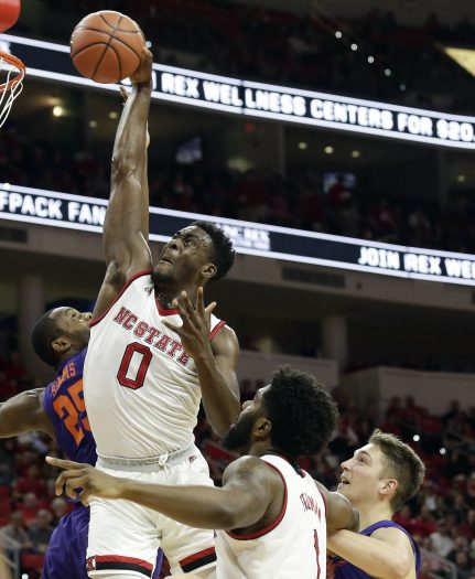 Clemson's Aamir Simms (25) defends as North Carolina State's Abdul-Malik Abu (0) drives for a dunk during the first half of an NCAA college basketball game in Raleigh, N.C., Thursday, Jan. 11, 2018. North Carolina State's Lennard Freeman and Clemson's Mark Donnal are at right. (AP Photo/Gerry Broome)