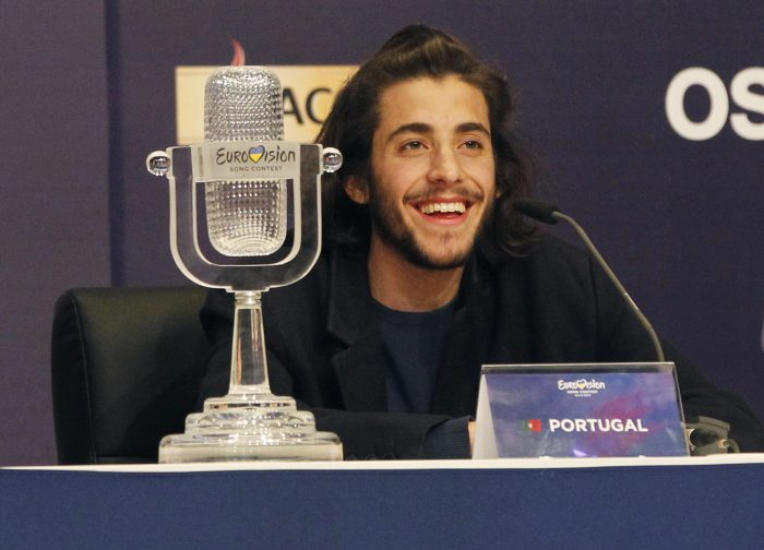 """FILE - In this Saturday, May 13, 2017 file photo, Salvador Sobral from Portugal smiles as he speaks after winning the Final of the Eurovision Song Contest with his song """"Amar pelos dois"""" during a press conference in Kiev, Ukraine. Salvador Sobral has left a Portuguese hospital after a successful heart transplant he underwent in December 2017. (AP Photo/Sergei Chuzavkov, File)"""