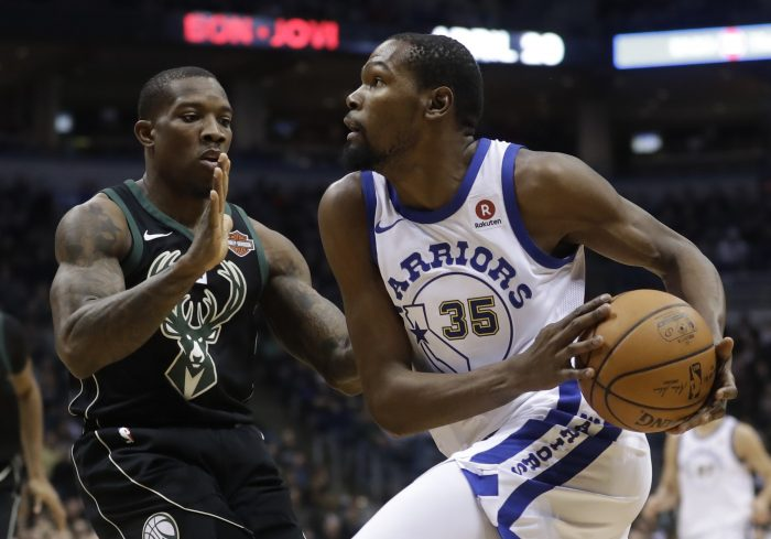 Golden State Warriors' Kevin Durant drives past Milwaukee Bucks' Eric Bledsoe during the first half of an NBA basketball game Friday, Jan. 12, 2018, in Milwaukee. (AP Photo/Morry Gash)
