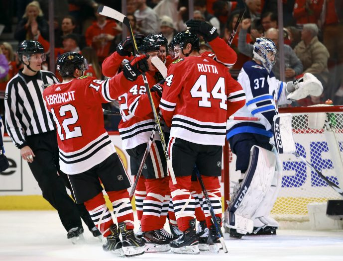 Chicago Blackhawks defenseman Jan Rutta (44) celebrates with teammates after his goal as Winnipeg Jets goaltender Connor Hellebuyck (37) stands in the net during the second period of an NHL hockey game Friday, Jan. 12, 2018, in Chicago. (AP Photo/Jeff Haynes)