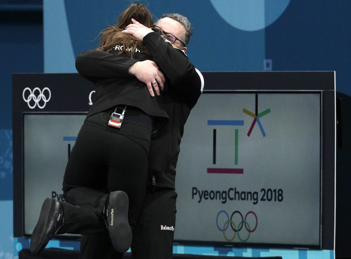 Russian coach, Vasily Gudin, right, embraces Russian curler Anastasia Bryzgalova after winning the bronze medal during their mixed doubles curling match against Norway at the 2018 Winter Olympics in Gangneung, South Korea, Tuesday, Feb. 13, 2018. (AP Photo/Aaron Favila)