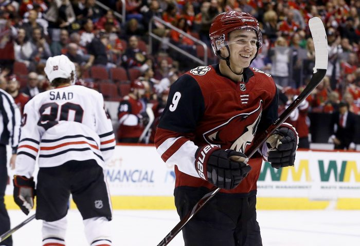 Arizona Coyotes center Clayton Keller (9) smiles as he celebrates a goal by Coyotes' Alex Goligoski as Chicago Blackhawks left wing Brandon Saad, left, skates back to the bench during the second period of an NHL hockey game Monday, Feb. 12, 2018, in Glendale, Ariz. (AP Photo/Ross D. Franklin)