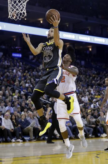 Golden State Warriors' Stephen Curry (30) drives past Phoenix Suns' Elfrid Payton (2) during the first half of an NBA basketball game Monday, Feb. 12, 2018, in Oakland, Calif. (AP Photo/Marcio Jose Sanchez)