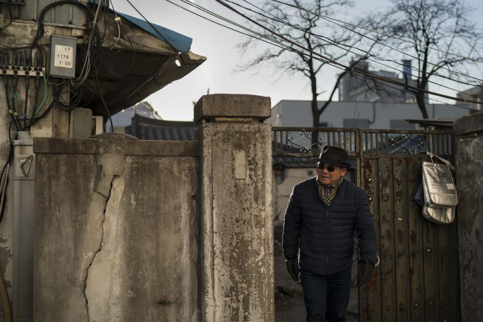 Song Hong, walks in downtown Gangneung, South Korea, Monday, Feb. 12, 2018. Song and his wife, Chong, arrived with their son, daughter-in-law and two grandchildren last week to explore a very different city than the one they left behind in 1975. The most elite athletes in the world now live, for a few weeks, in the high-rise apartment buildings of the Olympic Village with an address he'd never dreamed he'd see attached to such prestige: Gangneung.  (AP Photo/Felipe Dana)