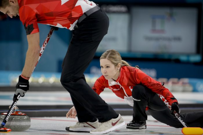 Canada's Kaitlyn Lawes, right, throws a stone as teammate John Morris sweeps the ice during the mixed doubles final curling match against Switzerland Jenny Perret and Martin Rios at the 2018 Winter Olympics in Gangneung, South Korea, Tuesday, Feb. 13, 2018. (AP Photo/Natacha Pisarenko)