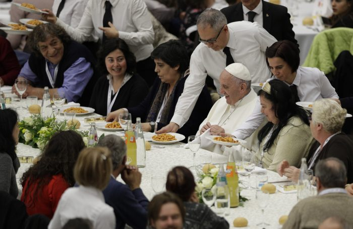 FILE - In this Nov. 19, 2017 file photo, Pope Francis is served gnocchetti during a lunch with several hundred poor people, at the Vatican on World Day of the Poor. When Cardinal Mario Jorge Bergoglio appeared five years ago, on March 13, 2013, at the main window of St. Peter's Loggia in a white cassock and without solemnity greeted the chanting crowd in the square with a casual 'buonasera' (good evening) it was immediately apparent that Pope Francis's style would be different, folksier than that of other popes.  (AP Photo/Andrew Medichini, files)