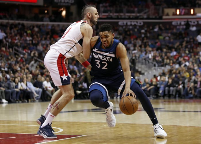 Minnesota Timberwolves center Karl-Anthony Towns (32) drives against Washington Wizards center Marcin Gortat (13), from Poland, during the first half of an NBA basketball game, Tuesday, March 13, 2018, in Washington. (AP Photo/Alex Brandon)