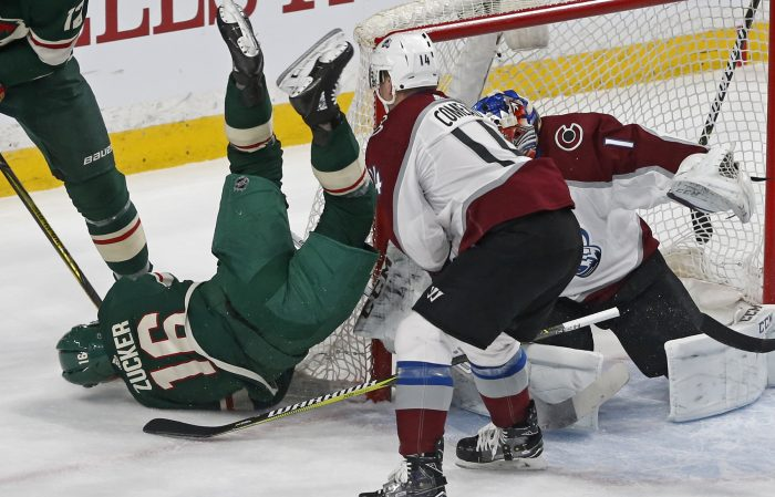 Minnesota Wild's Jason Zucker, left, tumbles to the ice over Colorado Avalanche goalie Semyon Varlamov, of Russia, in the first period of an NHL hockey game, Tuesday, March 13, 2018, in St. Paul, Minn. Zucker was helped off the ice after the fall. (AP Photo/Jim Mone)