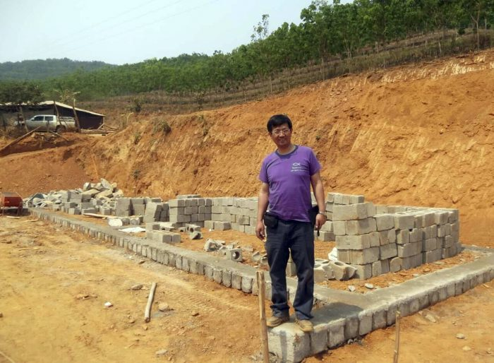 "In this May 2014, photo released by Ben Cao, Rev. John Sanqiang Cao breaks a ground on a new school in Wa State, Myanmar. The prominent Chinese pastor who has been detained by Chinese authorities since March 5, 2017 was sentenced in March 2018 to seven years in prison for ""organizing others to illegally cross the border."" (Ben Cao via AP)"