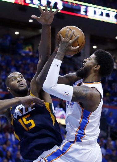 Oklahoma City Thunder forward Paul George, right, shoots as Utah Jazz forward Derrick Favors (15) defends in the first half of Game 1 of an NBA basketball first-round playoff series in Oklahoma City, Sunday, April 15, 2018. (AP Photo/Sue Ogrocki)