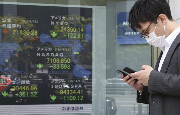 A man walks by an electronic stock board of a securities firm in Tokyo, Monday, April 16, 2018. Shares were mixed in Asia after an upbeat start to the week, with Chinese benchmarks leading the retreat. The air strikes on Syria appeared to be having scant impact on trading Monday. (AP Photo/Ng Han Guan)