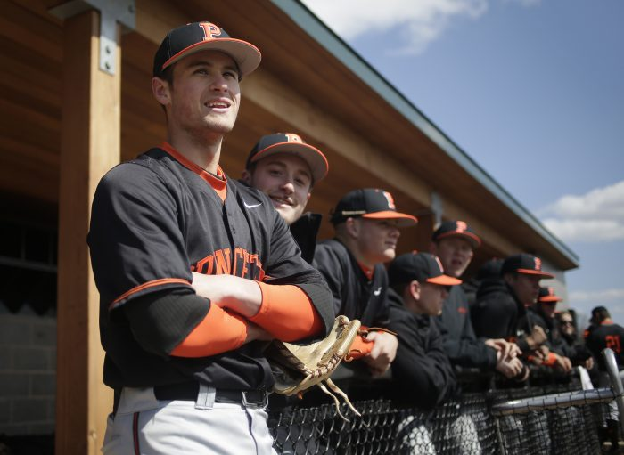 Princeton Tigers' Jake Boone, left, looks over the field before their game against the Monmouth Hawks in Princeton, N.J., Thursday, April 5, 2018. Boone is trying to put himself in position to make his the first four-generation major league family. His great-grandfather, Ray, was a two-time All-Star infielder from 1948-60. His grandfather, Bob, was a four-time All-Star catcher from 1972-90, then managed Kansas City from 1995-97 and Cincinnati from 2001-03. His father Bret, was a three-time All-Star second baseman in a big league career from 1992-05. And uncle Aaron is managing the New York Yankees. (AP Photo/Seth Wenig)