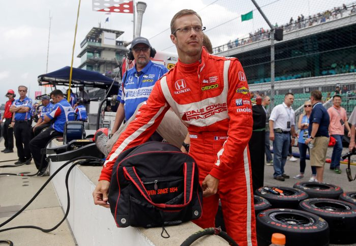 FILE - In this May 19, 2017, file photo, Sebastien Bourdais, of France, unpacks his helmet as he prepares to drive during a practice session for the Indianapolis 500 IndyCar auto race at Indianapolis Motor Speedway in Indianapolis. No matter the part, what Bourdais can do in a race car, and what kind of competitor he is at his core, have made it clear that he is still among the very elite at his craft. (AP Photo/Michael Conroy, File)