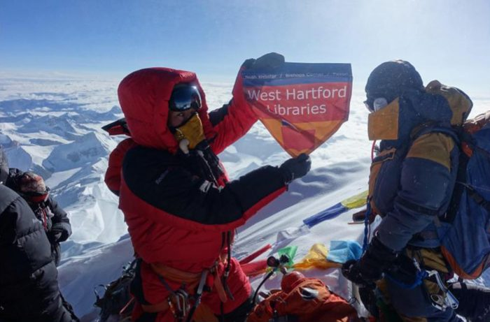 In this May 2017 photo provided by Lhakpa Sherpa, Sherpa displays a flag from West Hartford, Conn., on the summit of Mount Everest in Nepal. Once a year, Sherpa heads back to her native Nepal to try and break her own record for successful summits of Mount Everest by a woman. (Courtesy of Lhakpa Sherpa via AP)